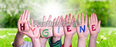 kids hands holding word hygiene grass