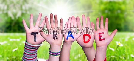 children hands building word trade grass