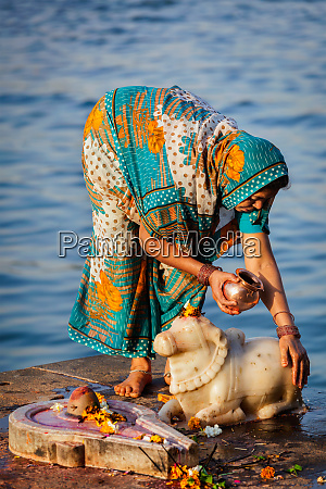 indian woman performs morning pooja on
