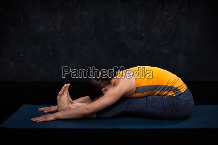 woman practices ashtanga vinyasa yoga asana
