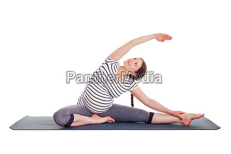 pregnant woman doing yoga asana parivrtta