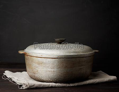 aluminum old cauldron on a wooden
