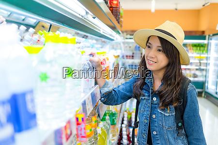 woman buy drink in supermarket