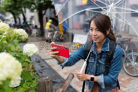 woman take photo on flower at