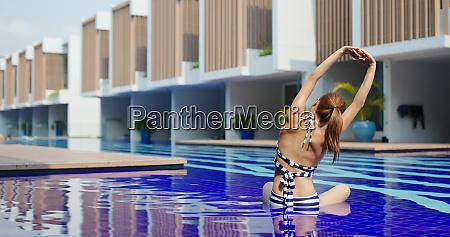 woman do yoga at swimming pool