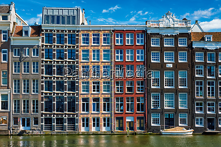 houses and boat on amsterdam canal