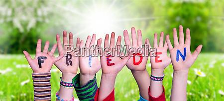 children hands building word frieden means