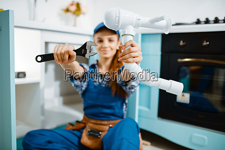 young female plumber shows wrench and