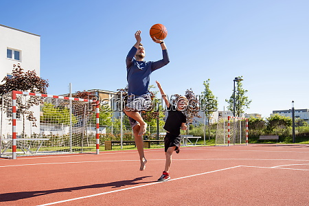 father and son playing basketball barefoot