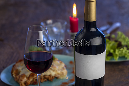 wine bottle and lasagna on wood