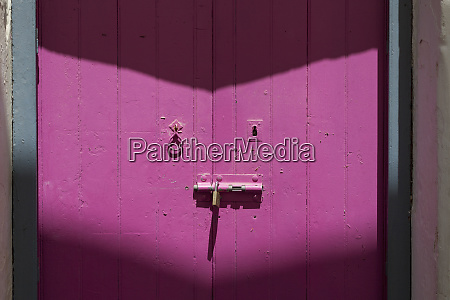 rusty padlock locking a pink wooden