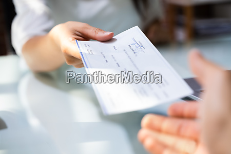 hand giving payroll compensation paycheck