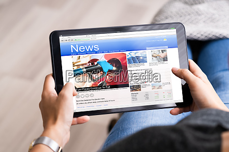 watching news on tablet computer