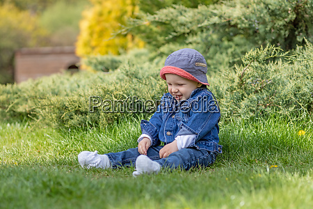 cute little baby boy sitting outdoors