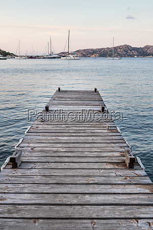 wooden pier and sailboats mooring in