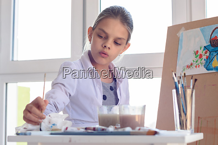girl artist concentrated wets brush in