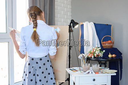 young artist standing draws behind the