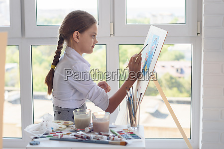 young artist paints watercolor paints on