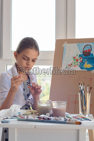 girl examines brush for drawing watercolor