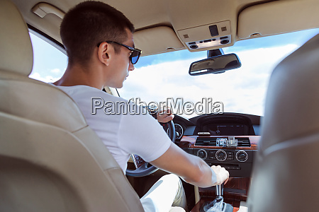 young stylish man in sunglasses driving