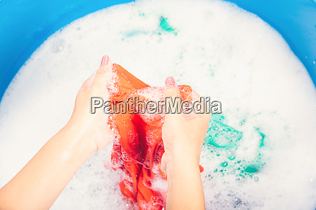 woman use hands washing color clothes