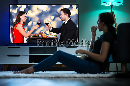 woman watching tv on couch or