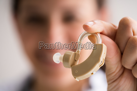 audiologist doctor holding hearing deaf aid
