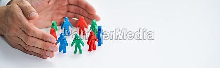 business executive hand protecting employee figures