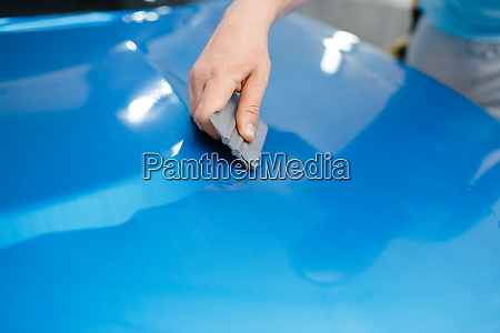 car wrapping mechanic with squeegee installs