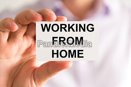 businessman holding working from home message