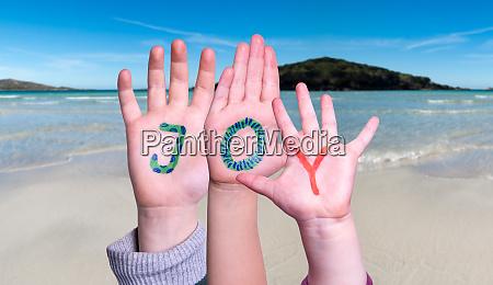 children hands building word joy ocean