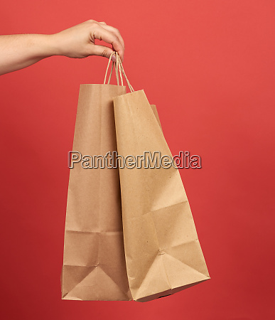 female hand holds a paper bag