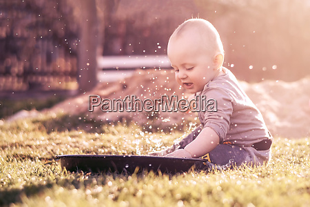 caucasian infant splashes water