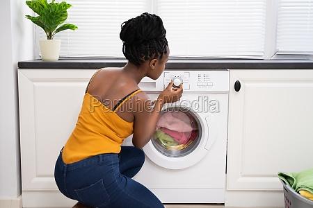 person hand setting washing machine