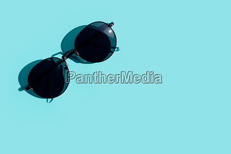 sunglasses on blue background copy space