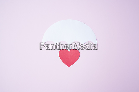 red paper heart shape under white