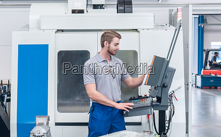 worker operating computer controlled machine tool