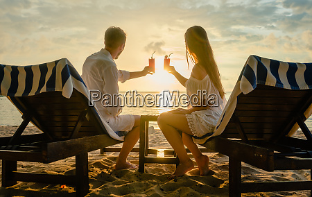 couple drinking cocktails on beach during
