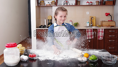 little girl is helping to bake