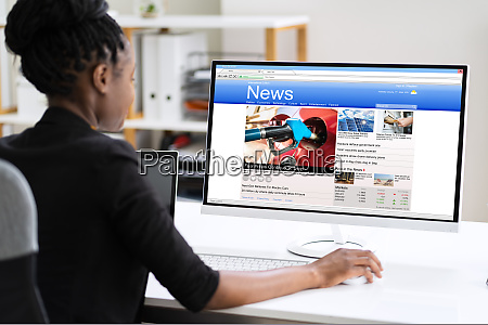 african woman looking at news in