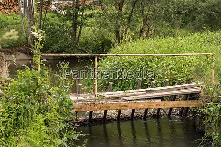 dangerous wooden bridge over stream