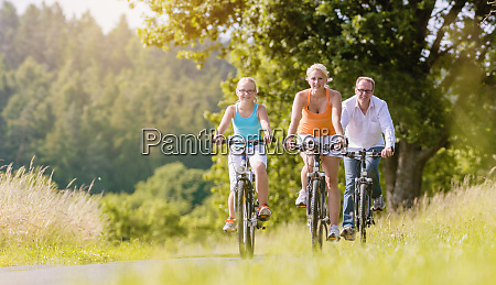 family having weekend bicycle tour outdoors