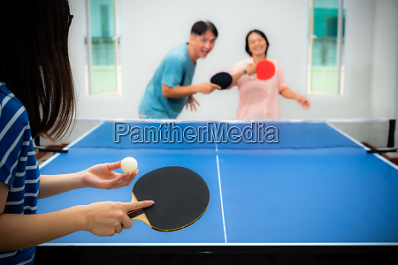 asian family fun playing table tennis