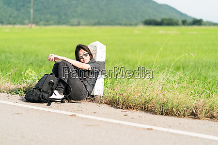 woman sit with backpack hitchhiking along