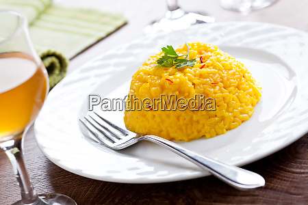 homemade saffron risotto with a glass