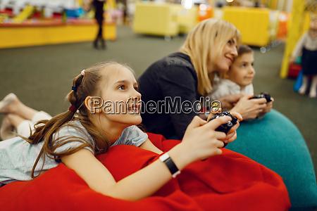 children plays game console entertainment center