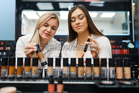 cosmetician and woman choosing nail varnish