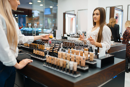 cosmetician at counter and woman cosmetics