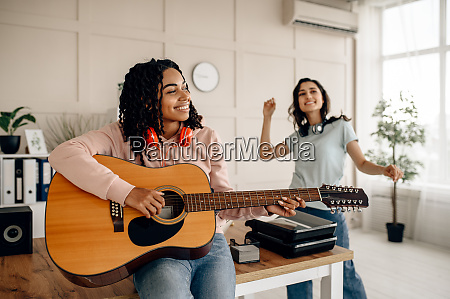 women play the guitar and listen