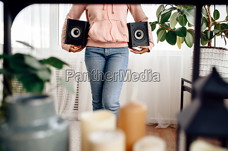 happy woman holds two audio speakers